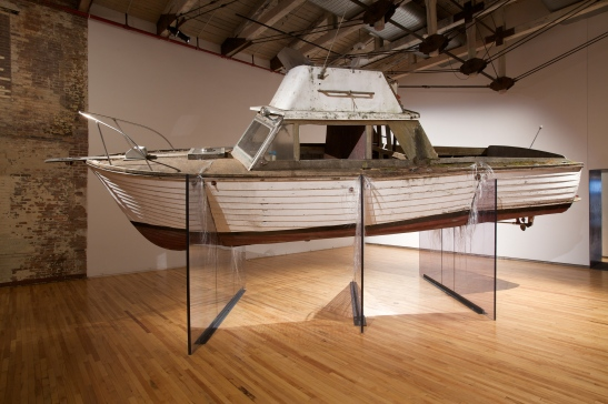 Nari Ward, Nu Colossus, 201, boat, metal, wood, metal chimney, copper drum, furniture, plexiglas and rubber roofing membrane, 720 x 336 x 168 inches (approximately) 1828.8 x 853.4 x 426.7 cm. In collaboration with MassMoCA North Adams, MA. Courtesy the artist and Lehmann Maupin Gallery, New York